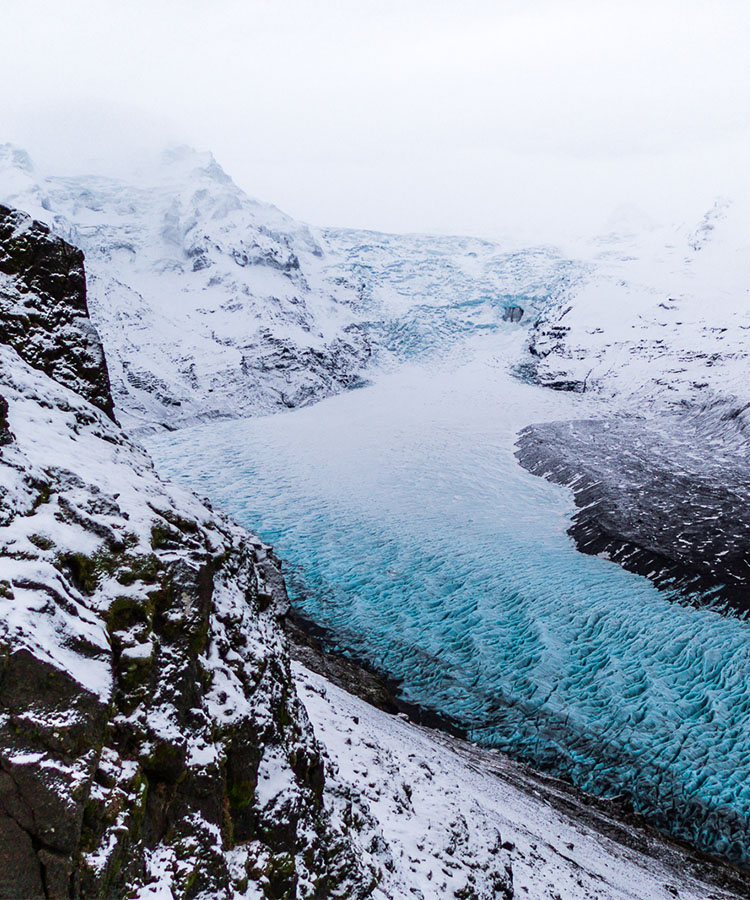 Snowy mountainside and blue waters running through them